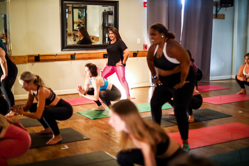 a yoga class with several women - the image focuses on one woman in hot pink leggings in a half-squat while the other yogis, also in squats, are blurred out