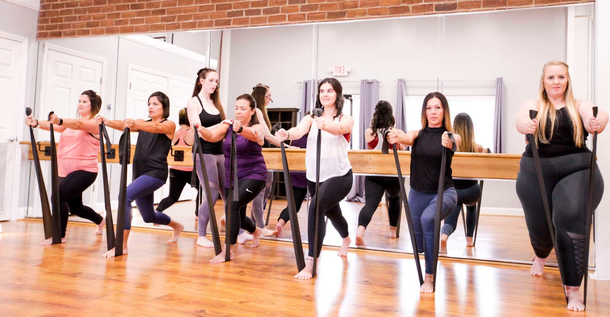 Image is of 6 students exercising by stretching a band. The instructor is standing behind them.