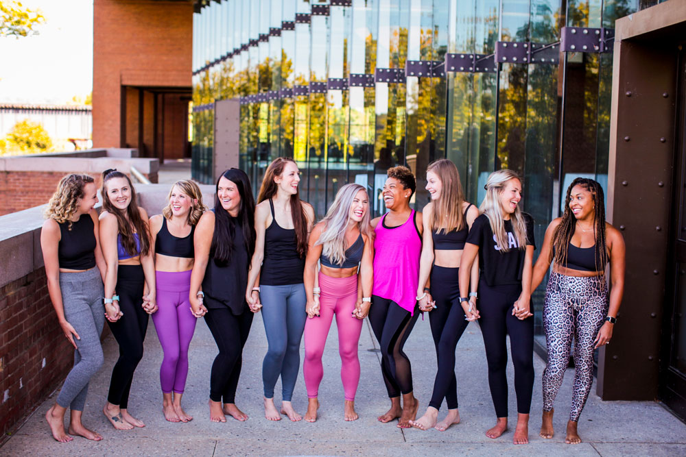a group of women in yoga clothing stand in a row, facing the camera, outside the Novo studio, talking and laughing