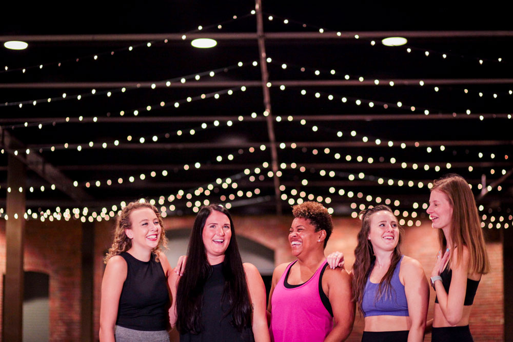a group of women in yoga clothes stand in a row in a classroom, laughing and talking. Above them from the rafters hang twinkling lights