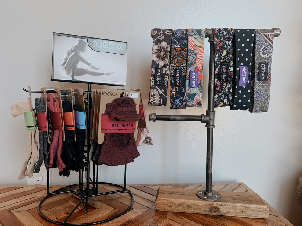 a selection of toe sox and violet love headbands hang from two tabletop display racks