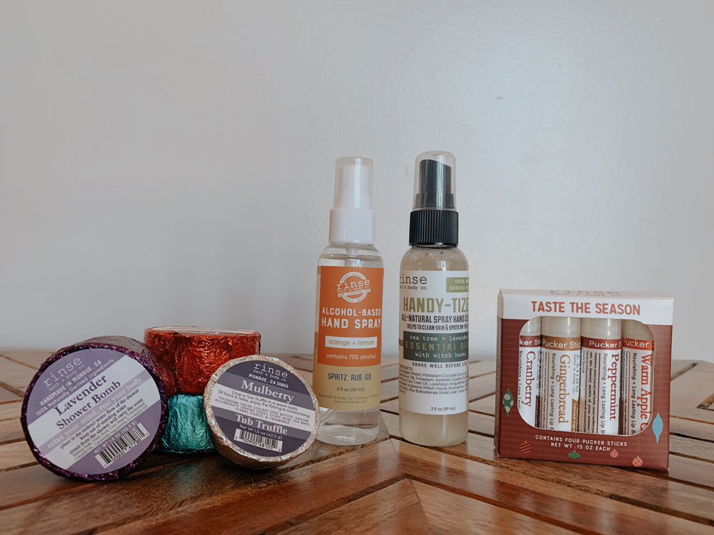 a selection of Rinse Bath & Body Co. soaps, sprays, and lip balms sit on a wooden table