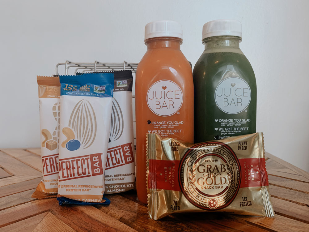 a selection of Perfect Bars, Juice Bar juices, and a Grab the Gold energy bar sit on a table top