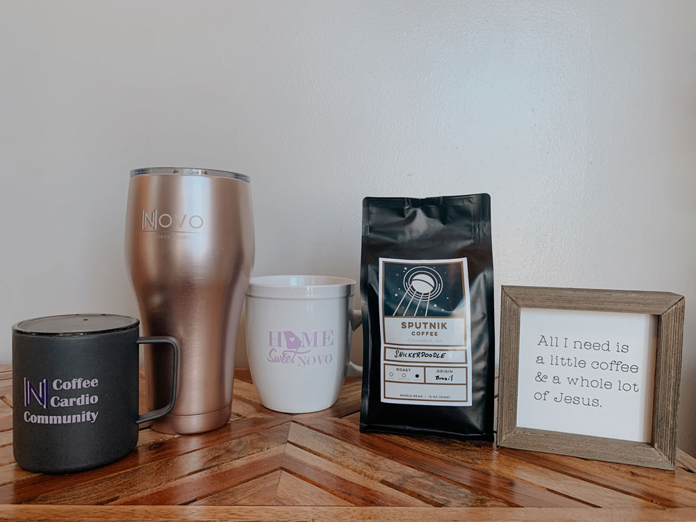 Three coffee mugs (one short black metal one with a lid, one tall rose-gold metal one with a lid, and one ceramic mug) sit next to a bag of Sputnik brand coffee beans in a Snickerdoodle flavor.