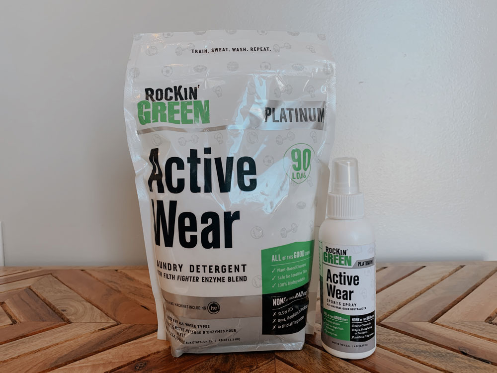 a bag of Rockin' Green Active wear laundry detergent and a small bottle of refresher spray sit on a wooden display tabletop