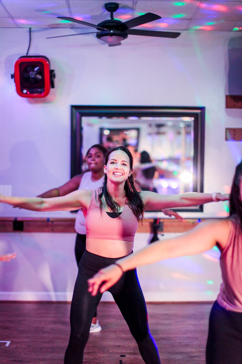 a woman in a pink sports bra and black leggings stands in a Novo classroom, smiling, facing the camera. Her legs spread and her arms extended out to the sides, parallel to the floor. The disco lighting of the 305 class shines on the walls and ceiling.