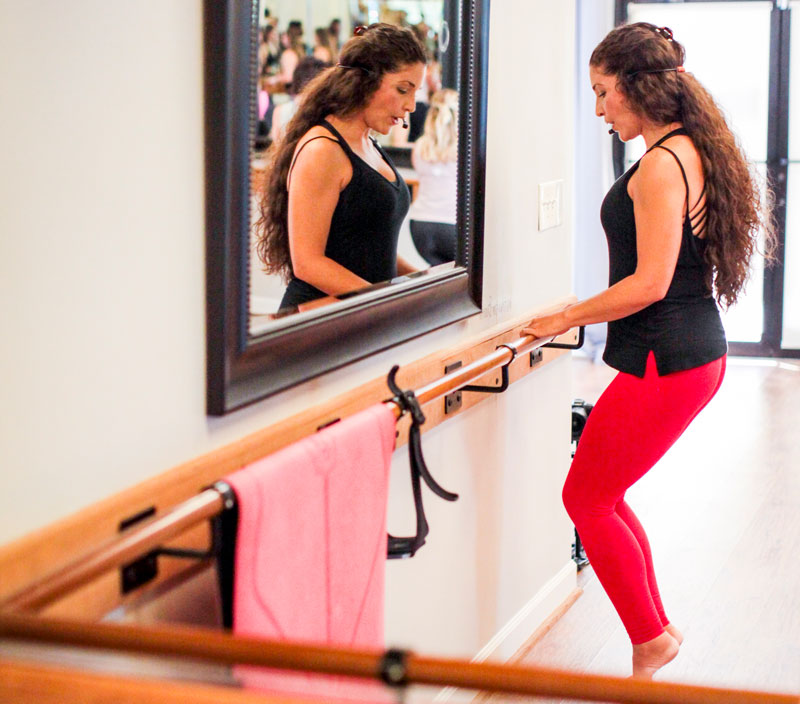 a Novo instructor in red leggings and a black sleeveless top stands at a barre, holding on to the barre with both hands, on her toes. A mirror hangs on the wall, reflecting the instructor's face to the class