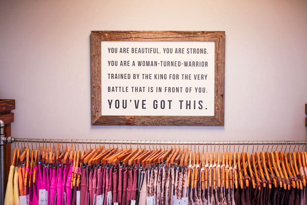 a rack of clothes sits against a wall with a large piece of art, framed with untreated wood. The art reads You are beautiful. You are strong. You are a woman-turned-warrior trained by the king for the very battle that is in front of you. You've got this.