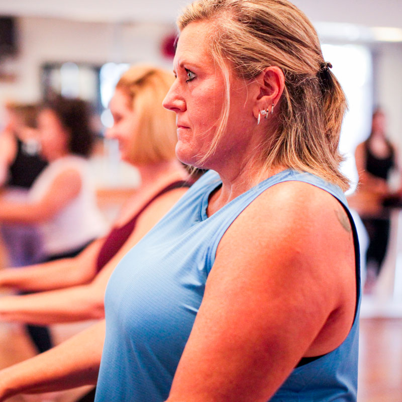 A blonde woman with a bob in a light blue sleeveless workout shirt stares intently into an off-camera mirror during a barre class