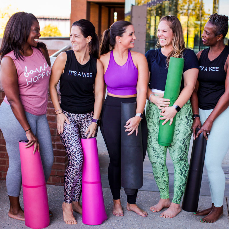 A group of five women stand outside the Novo studio, laughing and smiling at one another, while holding colorful yoga mats