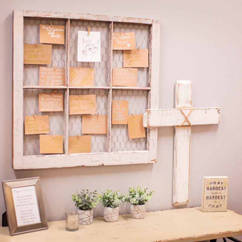 A decorative altar with an antique window frame hung to the wall, backed with wire, with inspirational notes attached to the wire with clothespins. Below the window frame is a table. Succulents, woodblocks with inspirational sayings, and a white wooden cross sit on the table.