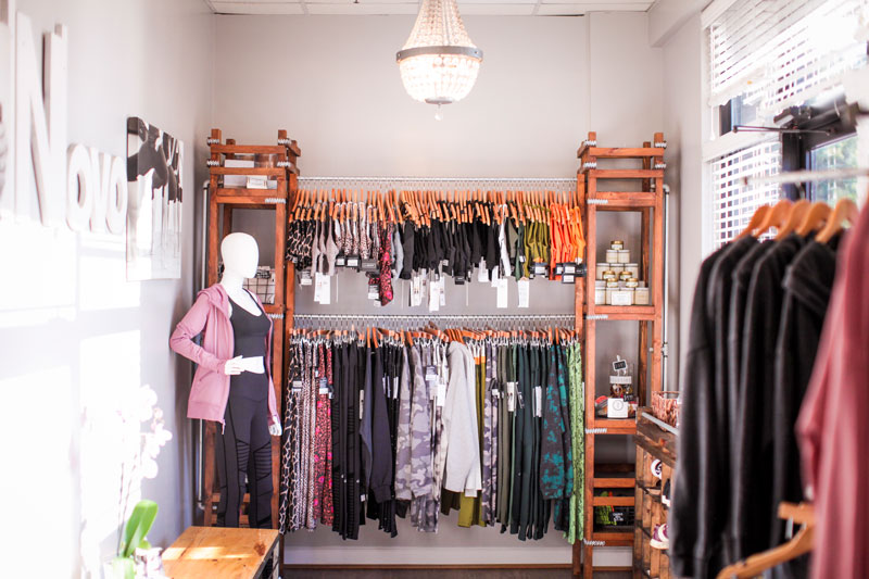 The Novo boutique - a wooden rack and shelf system with hanging workout clothes. A mannequin stands to the left.