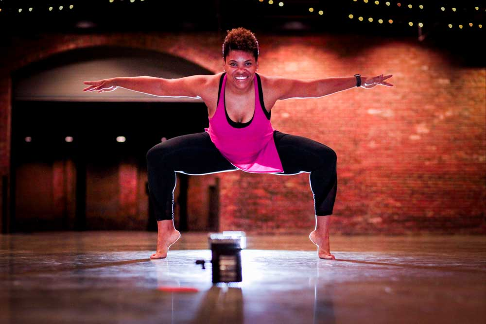 a woman with short, natural hair wearing a pink tank top and black leggings demonstrates a modern-dance inspired fitness pose. with her legs spread wide and her knees bent, she balances on the balls of her feet and exteds her arms out to her sides parallel to the floor
