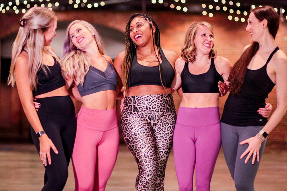 a group of women in fitness gear - leggings and tank tops - stand together in a studio. their arms wrap around behind one another, and they pose candidly, smiling and laughing at one another