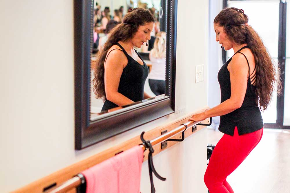 a woman with long, brown, curly hair wearing a black tank top and red leggings stands at a barre facing a wall, demonstrating a fitness move. a mirror on the wall in front of her reflects her face and the class behind her